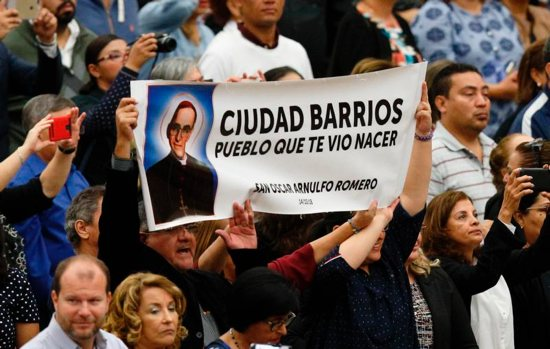 A man holds a banner with an image of new St. Oscar Romero during a Mass of thanksgiving to celebrate his canonization,