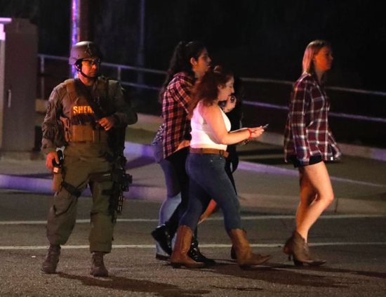 Women who fled from the shooting at the Borderline Bar and Grill in Thousand Oaks, Calif., pass by a sheriff's deputy Nov. 8 after a gunman killed at least 13 people. The gunman, who opened fire without warning late Nov. 7, was found dead inside the establishment, authorities said.