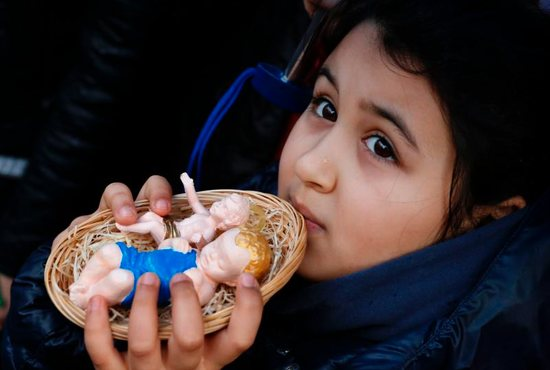 A girl in St. Peter's Square holds baby Jesus figurines for Pope Francis to bless during his Angelus at the Vatican. Children observed an annual tradition by bringing their Nativity figurines for the pope to bless.