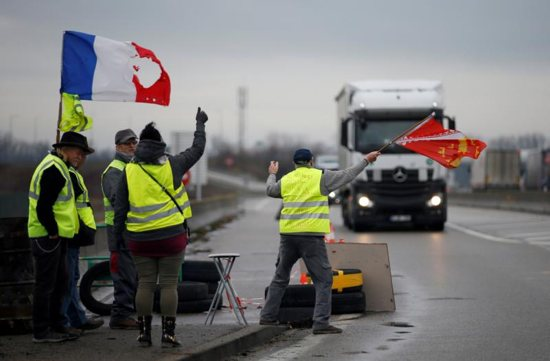 Protesters wearing yellow vests, the symbol of a French drivers' protest against higher diesel fuel taxes, occupy a roundabout Dec. 6 in Roppenheim, France.