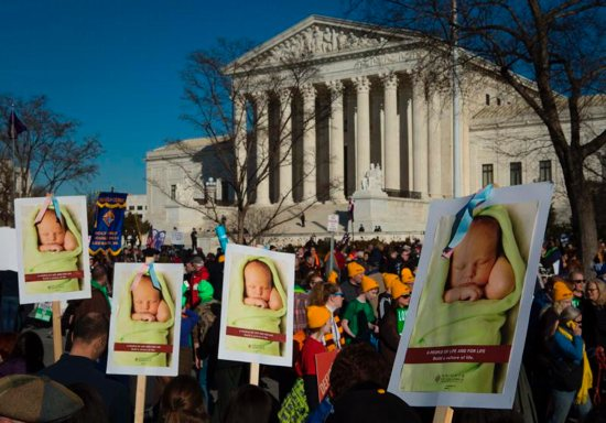 "Pro-life advocates gather near the U.S. Supreme Court in Washington Jan. 19, 2018. The novena ""9 Days for Life"" and related observances sponsored by the bishops' pro-life secretariat lead up to the annual Day of Prayer for the Legal Protection of Unborn Children Jan. 22, the anniversary of the Supreme Court's 1973 decisions in Roe v. Wade and Doe v. Bolton that legalized abortion."