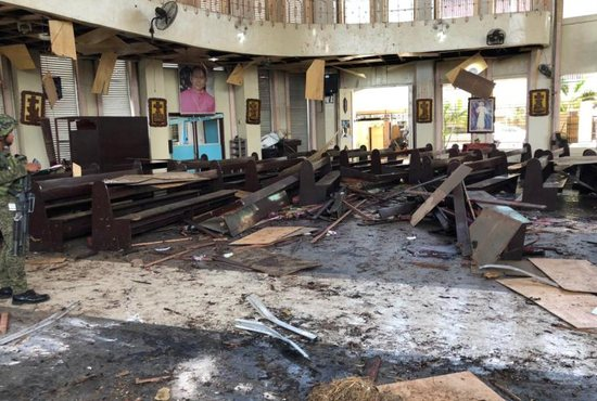 A Philippine army member inspects the damage inside the Cathedral of Our Lady of Mount Carmel in Jolo Jan. 27, 2019.