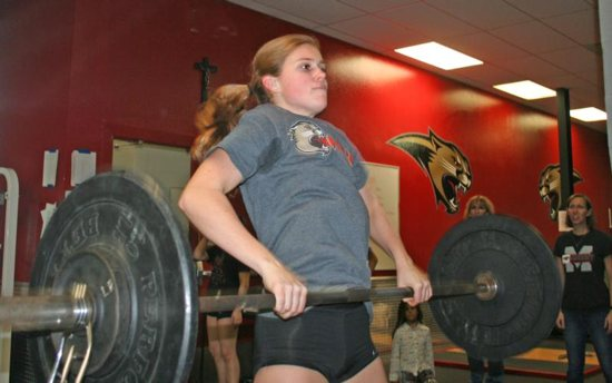 Grace Dickinson, a senior at Cardinal Mooney High School in Sarasota, Fla., performs a dead lift to an overhead press with 95 pounds as her coaches observe her Dec. 19, 2018. This is the inaugural year for the girls weightlifting team at the Florida Catholic school.