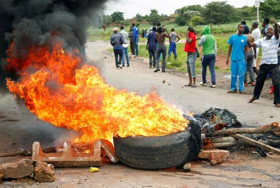 Protesters stand behind a burning barricade during protests over steep fuel price hikes Jan. 15 in Harare, Zimbabwe.