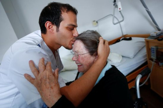 A woman in a Duesseldorf, Germany, receives a kiss from a retirement home employee Sept. 12, 2018. People cannot feel authentic compassion for others if they do not feel true love for Christ, Pope Francis said Feb. 1 during an audience with members of the Hospitaller Brothers of St. John of God.