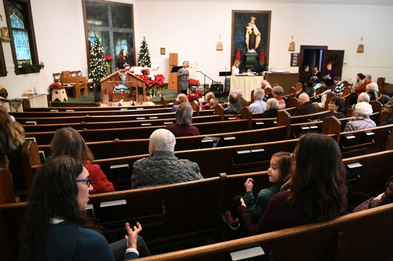 Sarah Novotny, left, uses sign language to communicate with her daughter, Audrey, 5, before Dec. 30 mass at Our Lady of Mount Carmel in northeast Minneapolis.