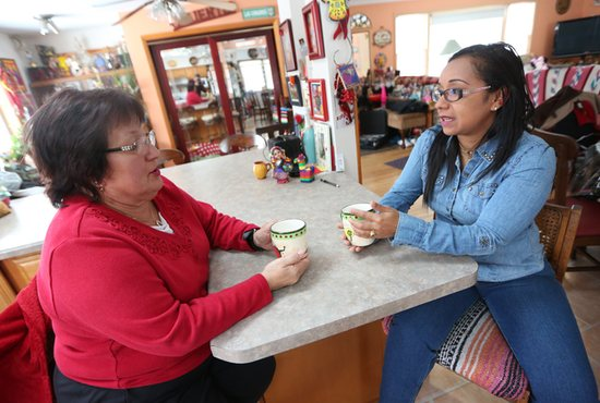 Zahyra Balza, right, talks with Debbie Luna of Our Lady of Guadalupe in St. Paul Feb. 14 in Luna's kitchen. Balza, who belongs to the Archdiocese of St. Paul and Minneapolis' mission parish in Venezuela, Jesucristo Resucitado, is visiting to collect donations and raise awareness of the struggles in her home country.