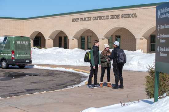 From left, freshmen Lucas Schoenecker and Laura Theis talk March 11 with sophomore Daniel Borbonio outside Holy Family Catholic High School in Victoria. All three live in Shakopee and benefit from Holy Family's efforts to boost enrollment by busing students into the school from beyond the school's usual Chaska-Chanhassen area.