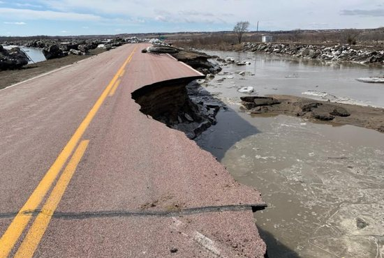 "A damaged road is seen March 16, 2019, after a storm triggered historic flooding in Niobrara, Neb. Gov. Pete Ricketts and the Nebraska National Guard surveyed flooded farms, homes, bridges and highways, damage Ricketts called ""devastating"" and perhaps the worst seen in a half-century."
