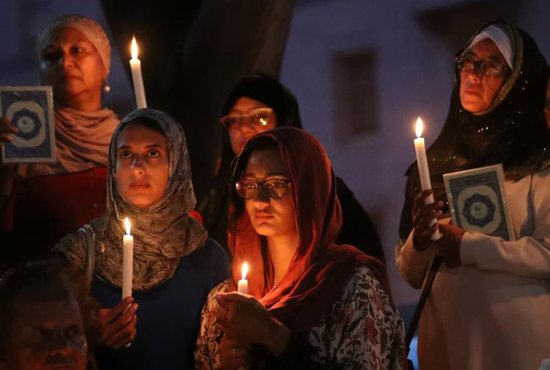 Women hold candles during a vigil outside St. George's Anglican Cathedral in Cape Town, South Africa, March 17, 2019, for the victims of the March 15 mosque attacks in Christchurch, New Zealand.