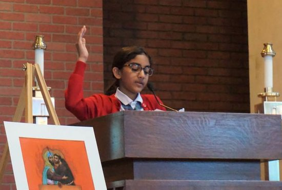 Shayla Chelliah, a sixth-grader at St. Francis International School in Hyattsville, Md., leads students in intercessory prayers March 22, 2019, during a school prayer service for victims of the New Zealand mosque shootings. Many of the speakers during the hourlong service addressed the need to put an end to hatred even in small ways at school.