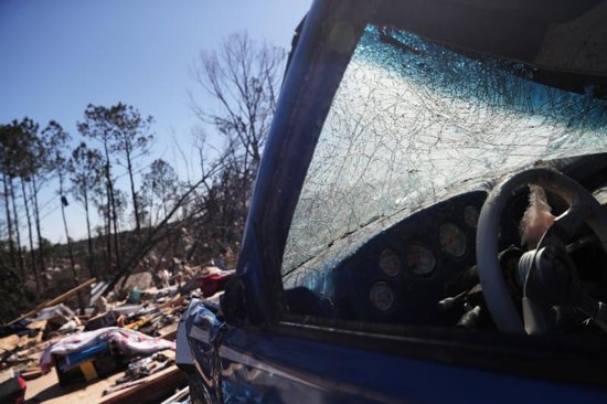 """A car and house are seen in Beauregard, Ala., March 5, 2019, after tornadoes ran through the area. Mobile Archbishop Thomas J. Rodi asked for prayers for """"those who lost their lives and their loved ones as well as those who have lost homes and businesses."""""""