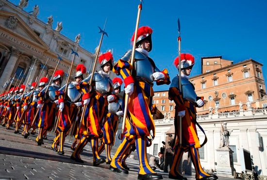 Swiss Guards march in St. Peter's Square at the Vatican Dec. 25, 2017. To better protect minors and vulnerable adults from all forms of abuse and exploitation, Pope Francis approved a new law and a set of safeguarding guidelines for Vatican City State and the Roman Curia.