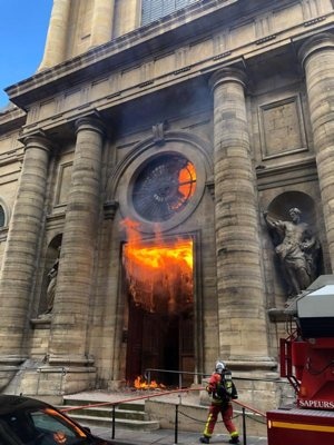 A firefighter is seen as flames shoot through the front door of St. Sulpice Church in Paris March 17, 2019, in this still image taken from social media. Vandals and arsonists have targeted French churches in a wave of attacks that has lasted nearly two months.
