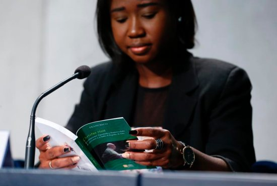"""Laphidil Oppong Twumasi, a youth leader from Ghana, reads Pope Francis' apostolic exhortation, """"Christus Vivit"""" (Christ Lives), during a news conference for its presentation at the Vatican April 2, 2019. The document contains the pope's reflections on the 2018 Synod of Bishops on young people, the faith and vocational discernment."""