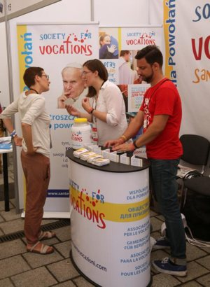"""A woman talks with a pilgrim at the World Youth Day evangelization center in Krakow, Poland, in this July 29, 2016, file photo. In a newly released document, Pope Francis said that to discern a vocation, people have to realize it's a calling from a friend, Jesus. The document, """"Christus Vivit"""" (""""Christ Lives""""), was the pope's reflection on the Synod of Bishops on young people, the faith and vocational discernment."""