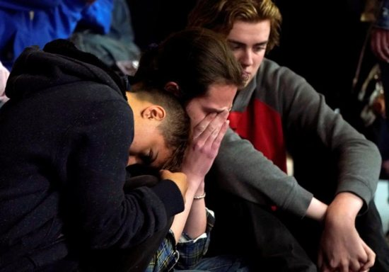 """Students mourn during a vigil May 8, 2019, for victims of a shooting at the STEM School Highlands Ranch in Colorado. Catholic leaders are calling for prayer and action in response to the May 7 shooting inside the charter school near Denver that focuses on science, technology, engineering and math. Kendrick Castillo, an 18-year-old Catholic senior was killed when he """"lunged"""" at one of the shooters to save others. Eight other students were wounded."""