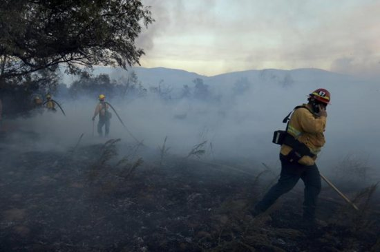 Firefighters work to put out hot spots in a fast moving wildfire