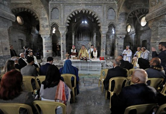 Syriac Catholic Archbishop Yohanna Moshe of Mosul, Iraq, center, concelebrates the liturgy at St. Thomas Syriac Catholic Church in the old city of Mosul Feb. 28, 2019. Announcing his desire to visit Iraq in 2020, Pope Francis called for a peaceful resolution to crises in the Middle East.