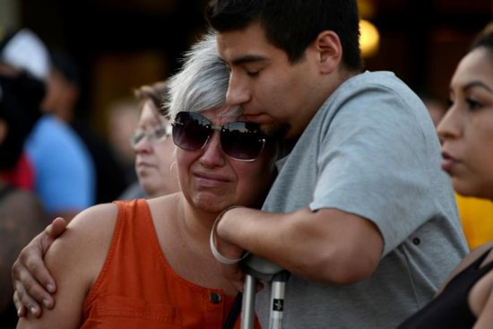 Justin Bates, a survivor of the Gilroy Garlic Festival mass shooting, and his mother, Lisa Barth, attend a candlelight vigil outside Gilroy City Hall in California July 29, 2019. The event honored those who died and were injured during the mass shooting at the fesitval a day earlier. The Diocese of San Jose held a bilingual prayer vigil July 29 for victims, survivors and first responders at St. Mary Church in Gilroy in response to the the shooting that claimed three lives and injured 12 others.
