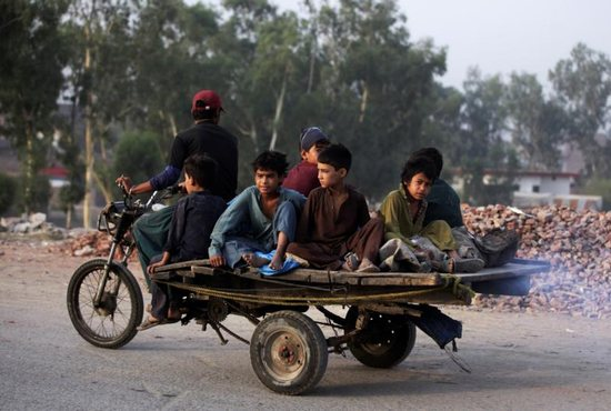 Boys from an Afghan refugee family ride on a motorcycle cart