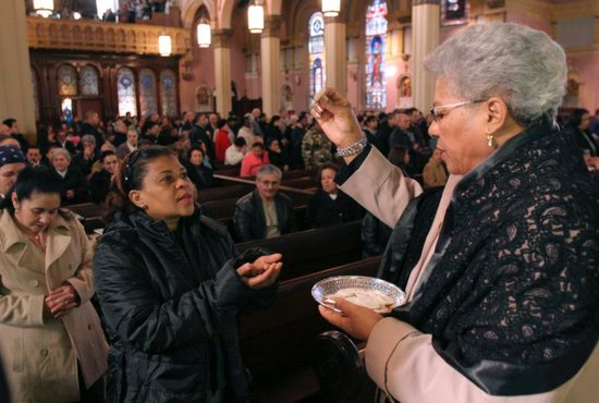 An extraordinary minister of holy Communion in Brooklyn, N.Y., distributes the Eucharist during Mass