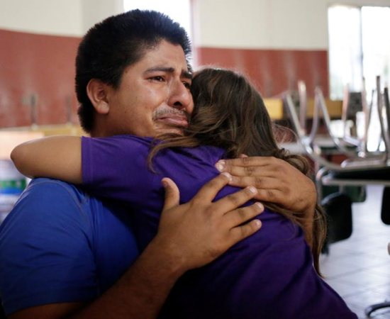 Salvadoran migrant Jose cries as he and his daughter embrace