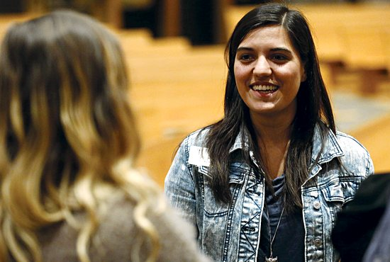 Gizzy Miko, a youth minister at St. Joseph of the Lakes in Lino Lakes, talks with people