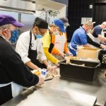 Archbishop Hebda helps serve noon meal to the homeless at Catholic Charities in St. Paul