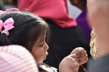 A girl holds a rosary before Pope Francis' speech at Independence Mall Sept. 26. (Sun photo | Katherine Long)