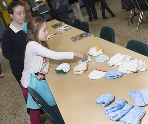 "St. Patrick's students Christabella Gilbank and Natalie Vanderwerken pick out a hat to be placed into a ""Welcome to the World"" bags as they and classmates make fifty bags to be given to the Lullaby Center at Oneida Health Care on Tuesday, Feb. 2, 2016 in Oneida N.Y. (Photo Special to The Catholic Sun by John Haeger)"