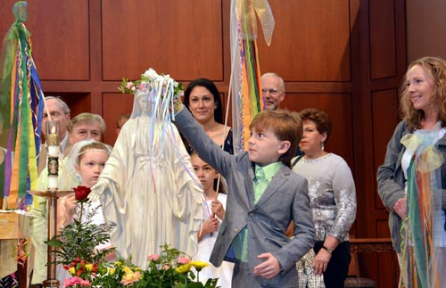 Luke Rombelcrowns Mary at Holy Cross Church in DeWitt May 8. (Photo courtesy Sister Rose Bill, MFIC)