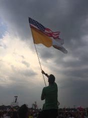 Syracuse Diocese pilgrim Joe Walters waves the American flag at opening Mass at Blonia Park. (Photo courtesy Samantha Pare)