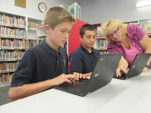 Judy DeLorenzo, library and media specialist at Holy Cross School, works with sixth-graders Luke Boule and Daniel Stark on Sept. 21. - SUN PHOTO | TOM MAGUIRE