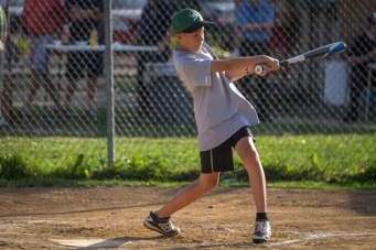 OLGC parishoner Noah Pangilinan swings while at bat during the Men In Black softball game in Endicott on Sunday.