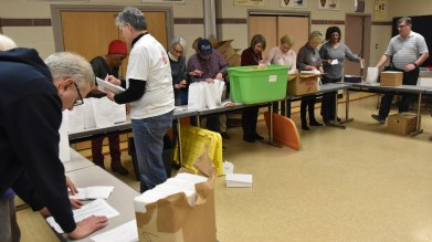 Keith checks paperwork - Jolly volunteers fill goodie bags for inmates