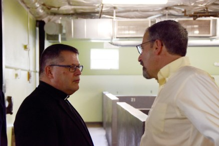 Bishop-elect Lucia speaks with Mike Melara, executive director of Catholic Charities for the Diocese of Syracuse, inside Catholic Charities' Men's Shelter
