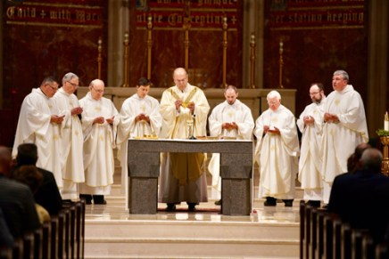 Concelebrates Mass with Bishop Robert J. Cunningham and several priests of the diocese