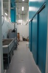 portrait picture of the dishpit with the electrical closet doors to the right and the 3 compartment sink to the left.