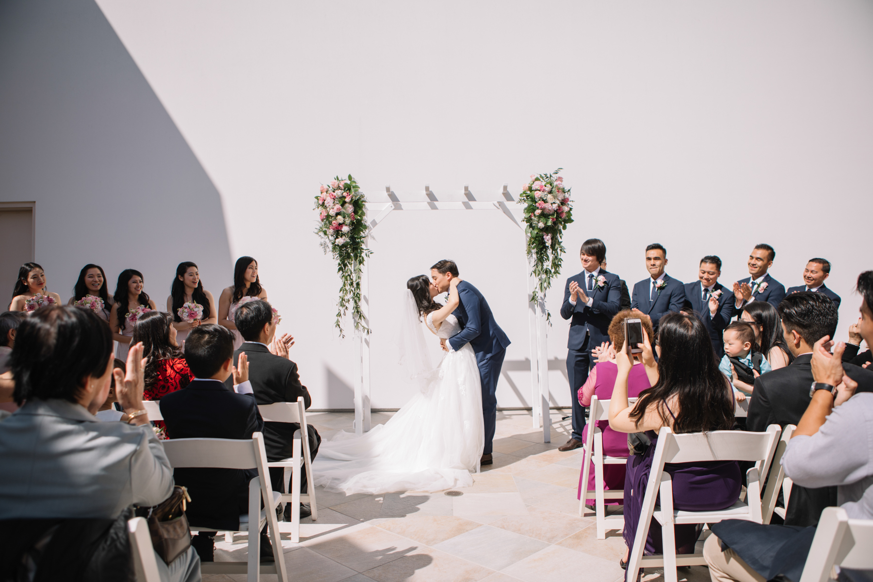 A small wedding venue outside with a bride and groom kissing in front of a white wall as their guests celebrate