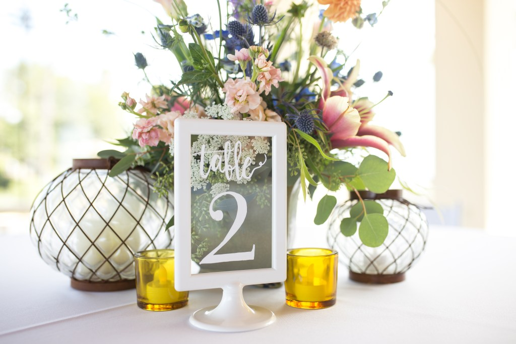A wildflower bouquet in the center of a round table with a white tablecloth. The table has the number two in a frame to mark the wedding table for guests, and four candles.
