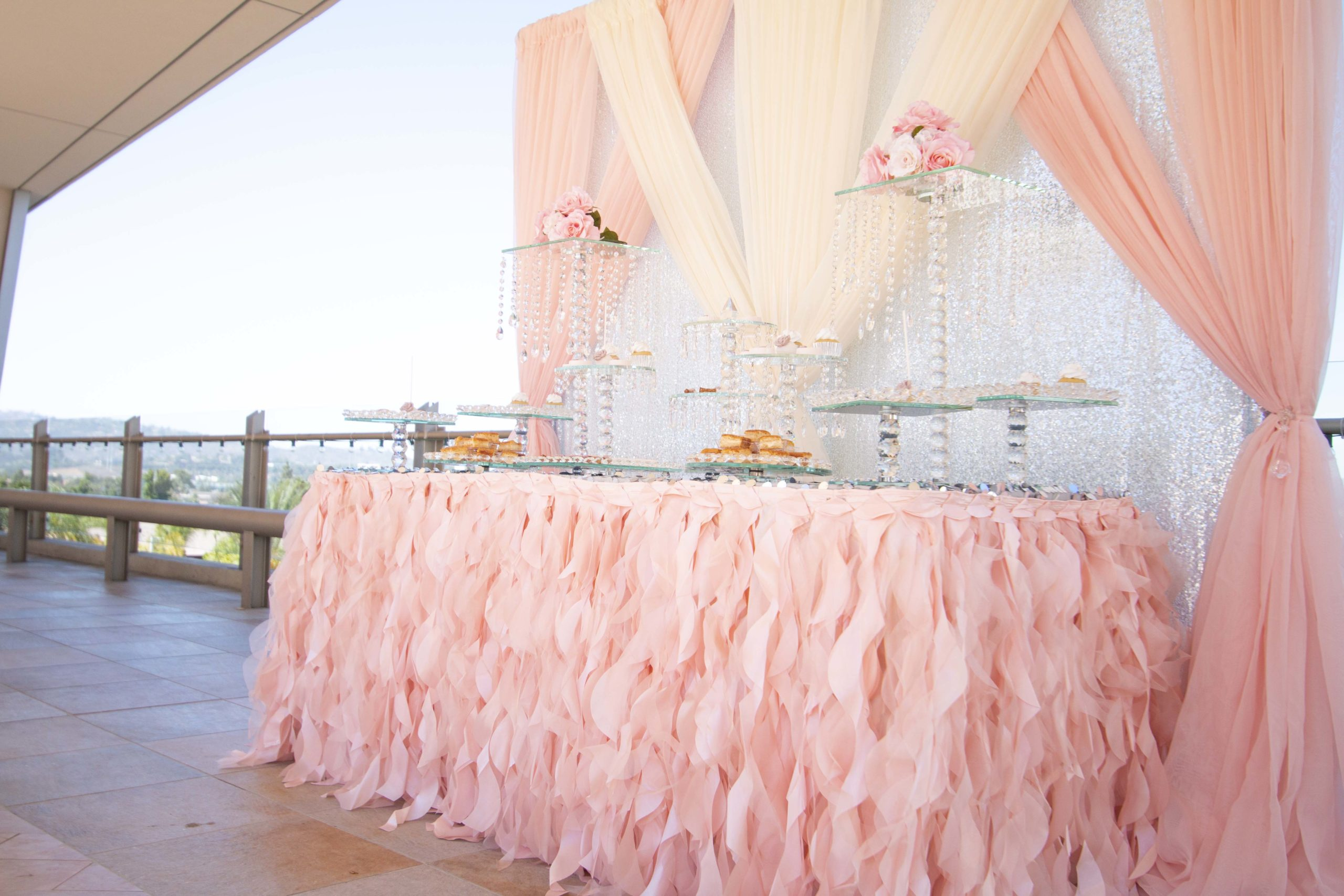 A monochromatic bridal shower theme with pinks and peaches adorning the dessert table in one of our outdoor venues in San Diego