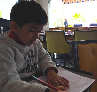 How to teach children - A boy reading and writing