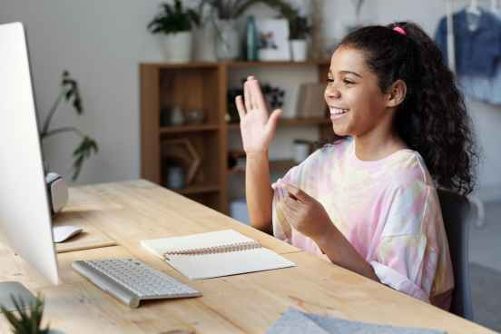 Child looking at the computer screen and raising hand