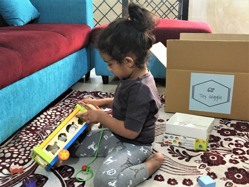 A girl playing with Toy Giggle toys