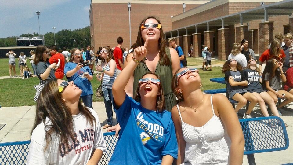 Juniors Kitty Case (left), Mary Gough (center), Katy Calderwood (right), and Campbell McCready (top) view the solar eclipse during 6th period. Many students had the opportunity to view the eclipse with glasses distributed by the Astronomy Club.