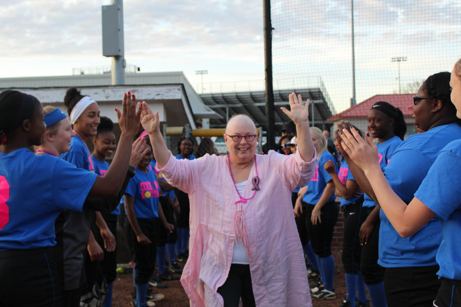 Dr. Barbara Lowe walks through the team huddle giving the players high fives. This is the team's first year helping with the event.