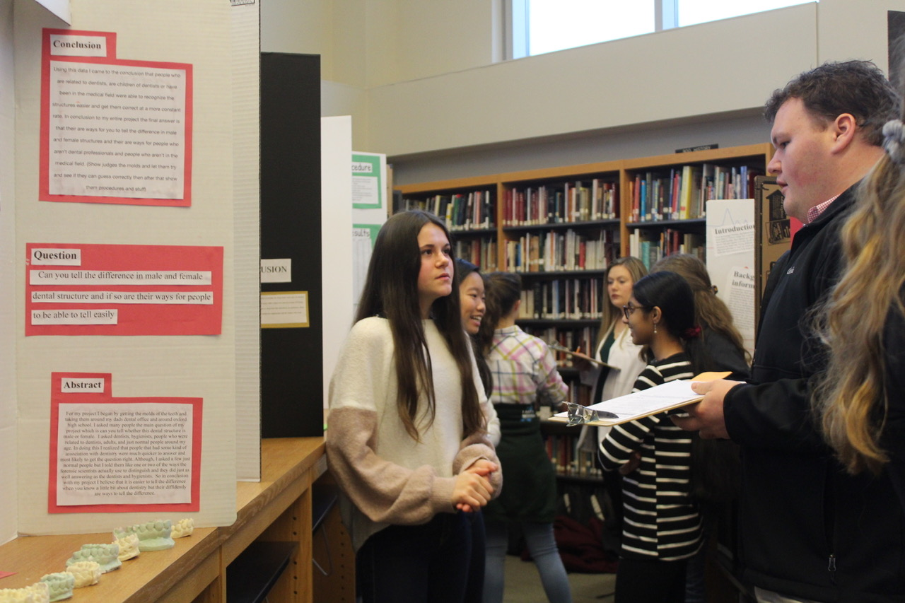 Freshman Ember Reysen presents her science fair project to one of the judges. The science fair took place on Jan. 23, and it allowed students to better their public speaking skills while learning new things about their topics.