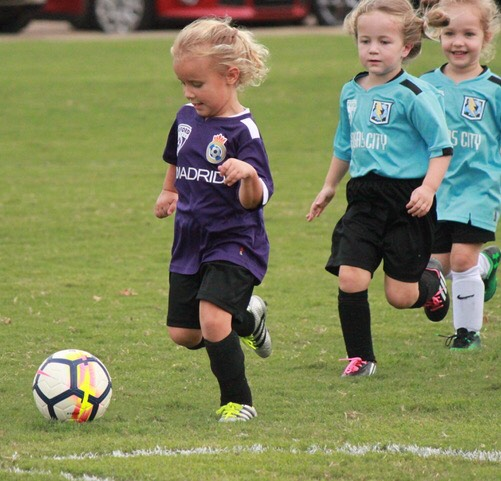 Three little girls run after the soccer ball during an OPC soccer game. Different OPC sports run throughout the whole year.