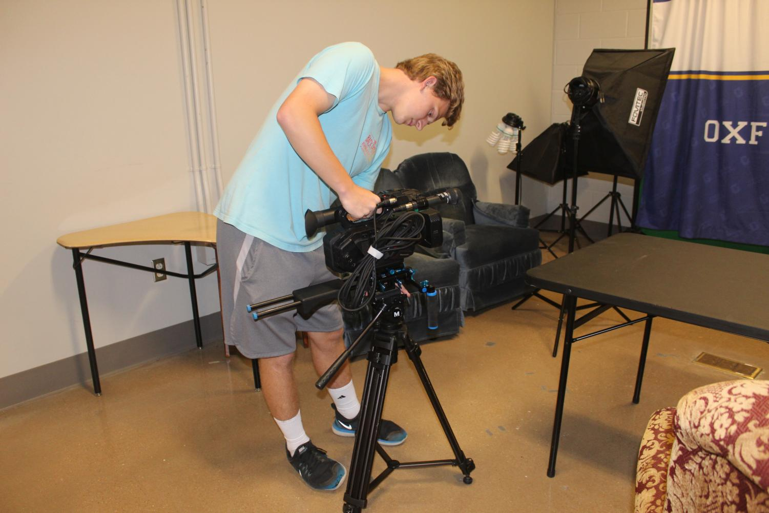 Senior Dalton Whitehead sets up a camera and gets ready to film a segment for